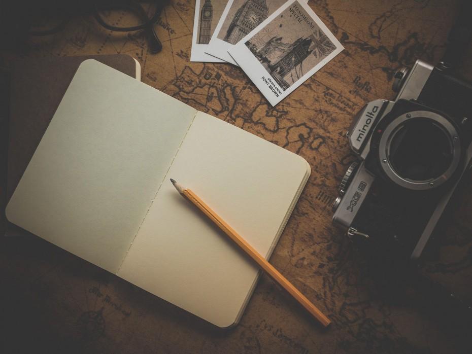 Illustrasjonsbilde av notatbok, kart og kamera